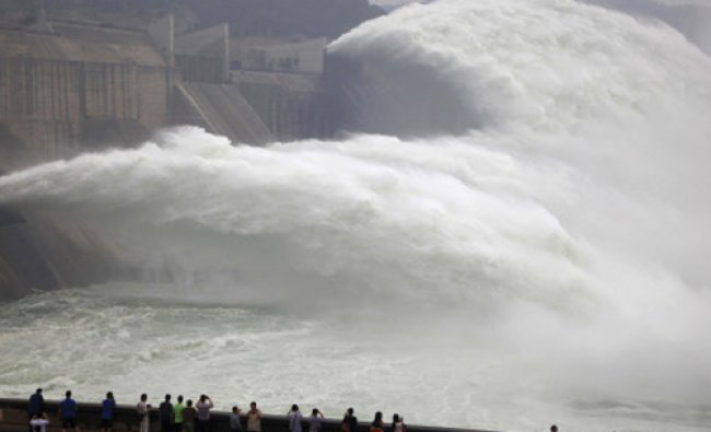 Visitors watch water gushing from the section of the Xiaolangdi Reservoir on the Yellow River...
