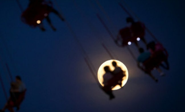 People ride the Luna Park Swing Ride as the Super Moon rises on Coney Island, June 22, 2013. The...