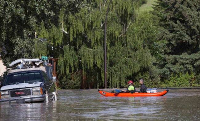 Two men ride their kayak down a flooded street after checking on their house in the community of...