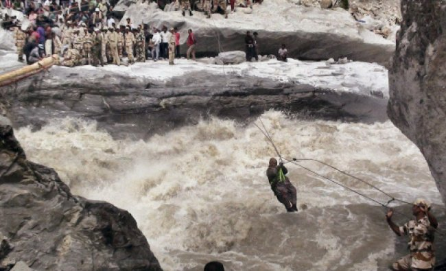 ITBP personnel rescuing a woman pilgrim with the help of a ropeway constructed above Alaknanda...