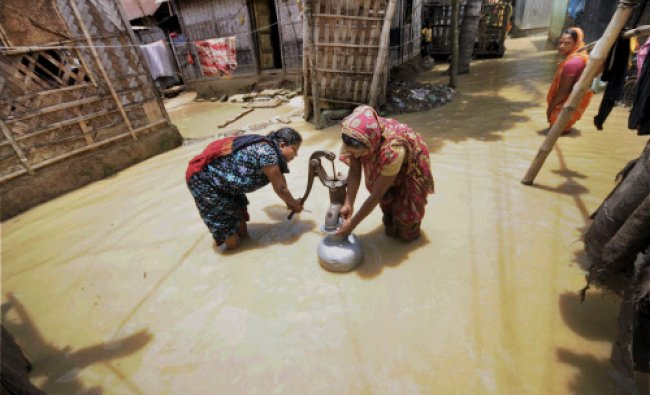 Women collecting water from a hand-pump at a flooded locality after heavy rains in Agartala...