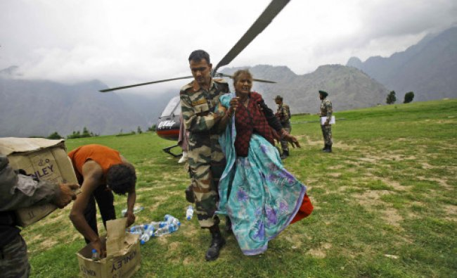 A soldier helps an injured pilgrim after she was rescued from the higher reaches of mountains...