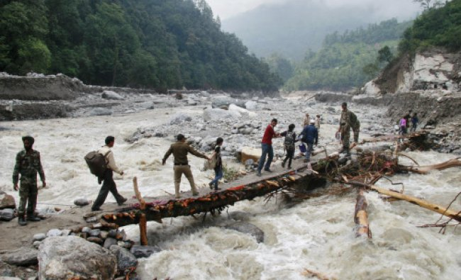 Army personnel help stranded people cross a flooded river after heavy rains in Uttarakhand...