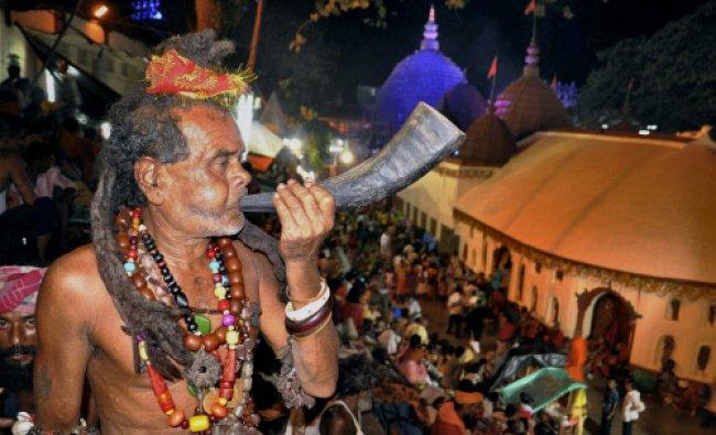 A Sadhu blowing a pipe made of Buffalo horn at the Kamakhya Temple during Ambubachi Mela in...