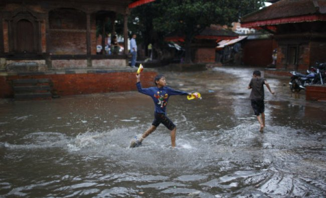 A boy throws a flip-flop towards his friend as they play on the waterlogged streets...