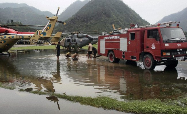 Fire fighters busy to clear water around parked relief helicopters after rains at Gauchar airbase ..