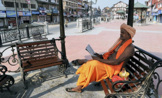 A sadhu reading newspaper near deserted Lal Chowk as security has been beefed up in Srinagar...