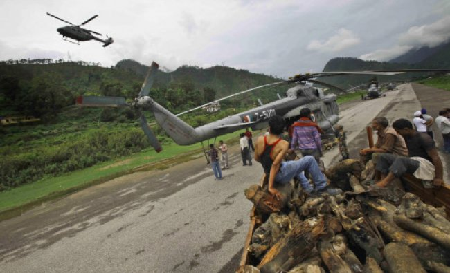 Locals unload woods from a truck to be loaded on to Indian Air force helicopters, in Gauchar...