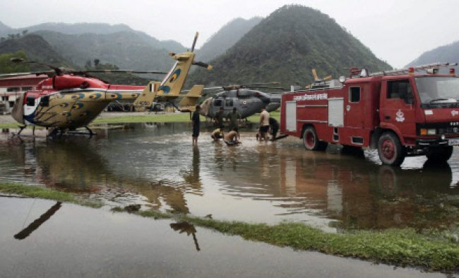 Fire fighters busy to clear water around parked relief helicopters after rains at Gauchar airbase..