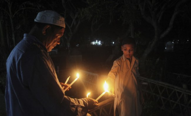 Muslims light candles to offer prayers near the graves of a loved one on Shab-e-Barat in Gauhati...