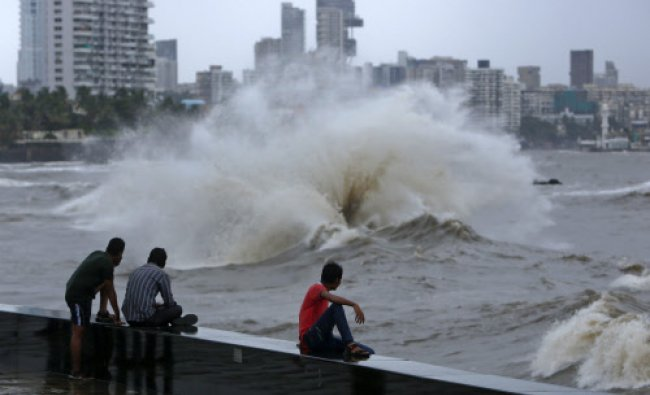 People watch waves from a sea wall at high tide during monsoon season in Mumbai June 25, 2013.