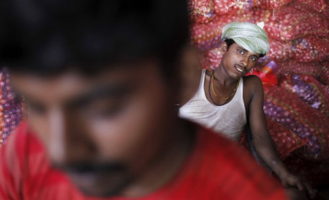 A laborer watches as he sits near bags of onions at a market in Allahabad, India...