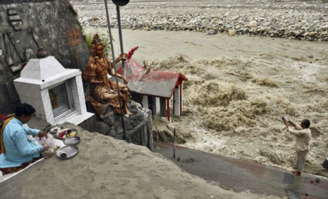 A devotee worhips at the bank of flooded Bhagirathi River in Uttarkashi on Monday.