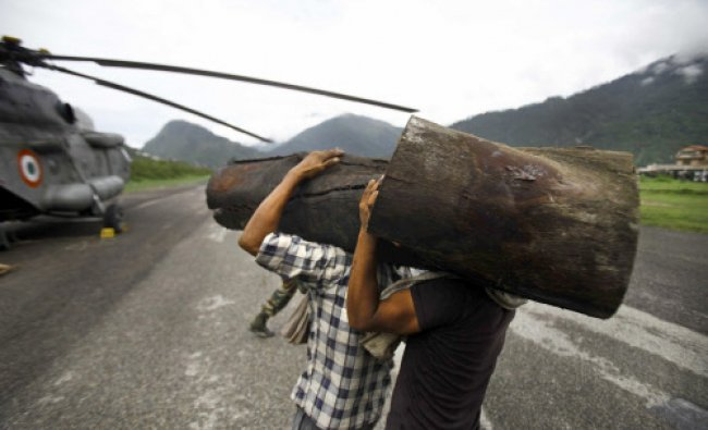 Locals load large pieces of wood on to an Indian Air force helicopter, in Gauchar,in the northern...