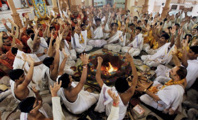 People perform a havan for the Uttarakhand flood victims at a temple in Ahmedabad, Gujarat...