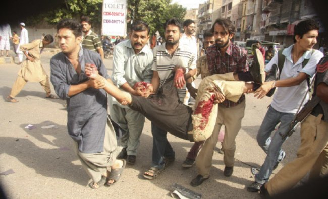 People carry an injured policeman at the site of a bomb blast in Karachi June 26, 2013...