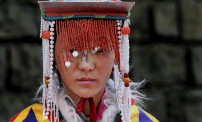A Tibetan follower waits for the arrival of the spiritual leader the Dalai Lama at a teaching...