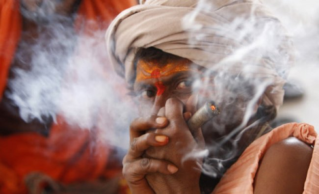 A holy man smokes as he waits to register for the annual pilgrimage to the Amarnath cave shrine...