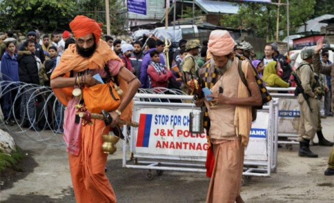 Sadhus walk towards the holy shrine of Amarnath as others wait at Chandanwari base camp...