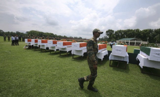 A soldier walks past flag-draped coffins containing the bodies of rescue personnel who died...