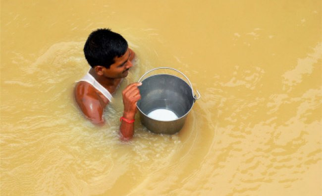 A man wades through flooded water with drinking water in Allahabad, Uttar Pradesh on Friday.