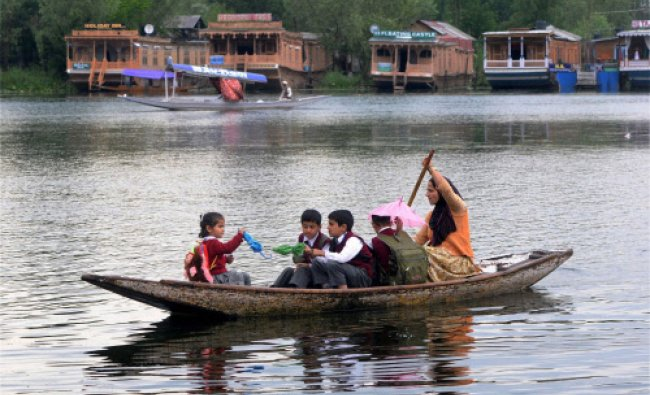 A woman with school children rows a boat across Dal Lake in Srinagar on Saturday. PTI Photo