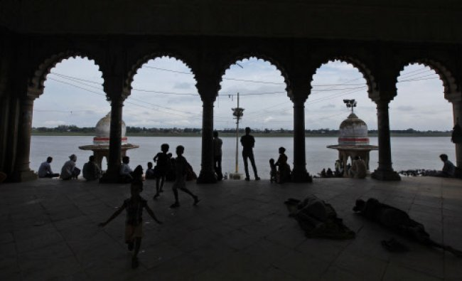 People rest on the banks of the River Yamuna in Allahabad, India, Friday, June 28, 2013.