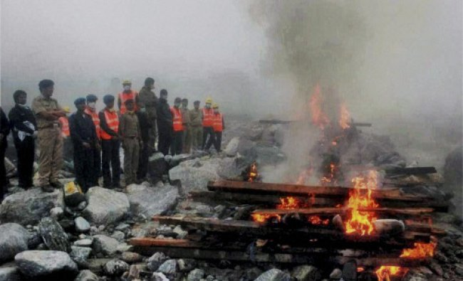 Uttarakhand police and NDRF personnel perform mass cremation of the pilgrims bodies in Kedarnath...