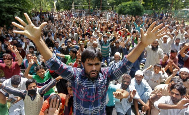 Villagers shout slogans during the funeral of Irfan Ahmad Ganaie, who was reportedly killed...