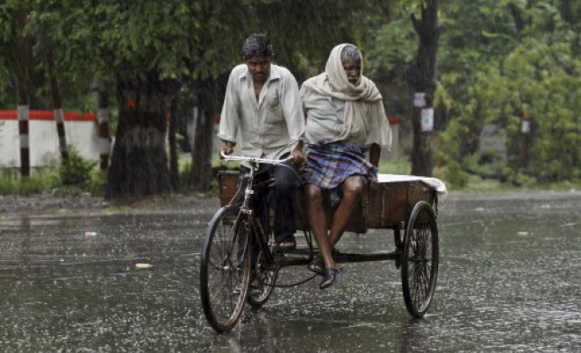 A man rides his cycle-cart as rain falls on a street in Allahabad, India, Sunday, June 30, 2013.