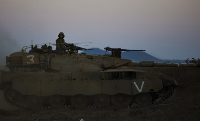 An Israeli soldier looks on from a tank during a drill in the Golan Heights