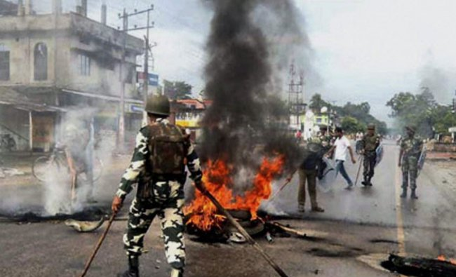 Security personnel dousing the flames after protesters burnt tyres during their bandh call
