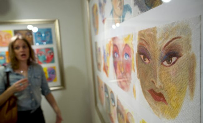 A woman stands near works by artist Ken Delmar at the George Billis Gallery in New York September...