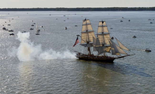 The U.S. Brig Niagara fires one of its guns while cruising east in Presque Isle Bay after leading...