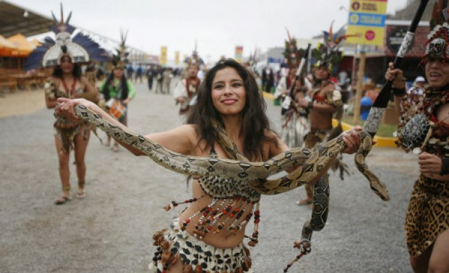 An Amazonian dancer performs while holding a snake during the Mistura gastronomic fair in Lima...
