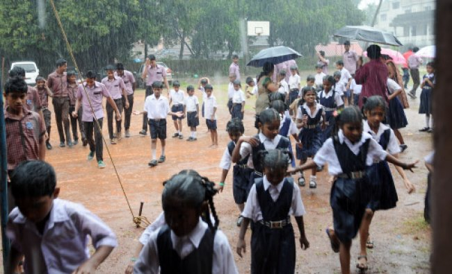 Students try to escape from heavy rainfall which lashed during a procession which was organised...