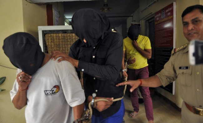 Police escort men accused of a gang rape, outside a police station in Noida