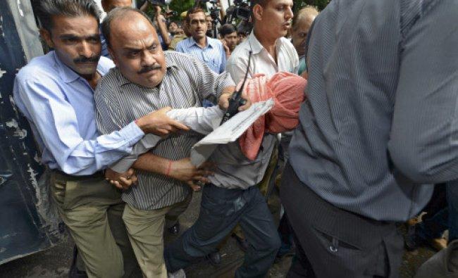 Plainclothes policemen escort a teenager to a juvenile court in New Delhi