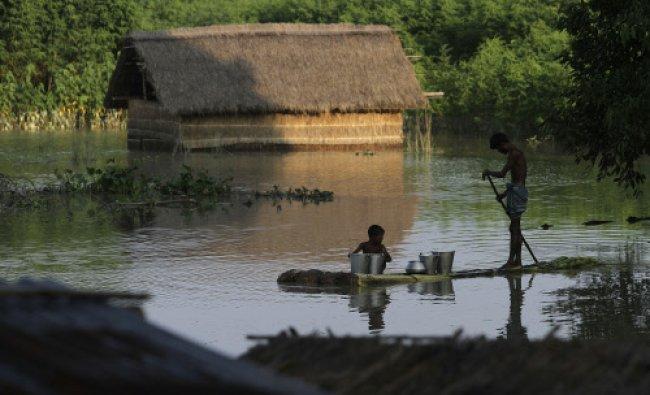 A man paddles a banana raft as he transports drinking water through flood waters in Burhaburhi...