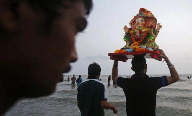 A devotee carries a statue of Ganesh, the deity of prosperity, into the Arabian Sea...