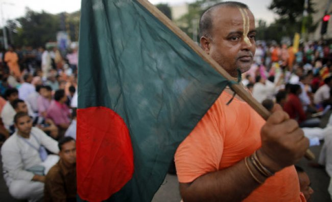 A Hindu monk holds a Bangladesh national flag as they block a street during a protest in Dhaka...