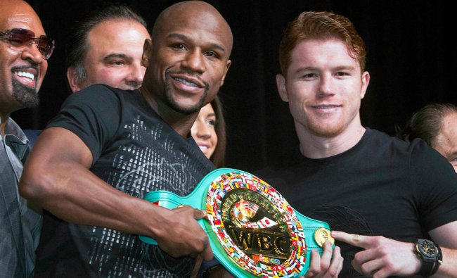 Undefeated boxers Floyd Mayweather Jr. (L) of the U.S. and Canelo Alvarez of Mexico pose with a...
