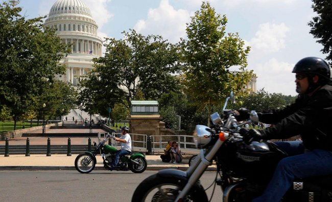 A small group of motorcyclists ride past the U.S. Capitol as part of an effort by riders to make...