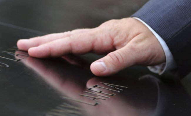 A mourner touches a name inscribe in the South Reflecting Pool of the 9/11 Memorial during the...