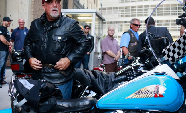 Singer Billy Joel gets off a motorcycle after riding from the Rescue 1 firehouse on West 43rd...