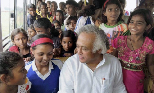 Union Minister for Rural Development Jairam Ramesh travel in a bus with tribal girls during...