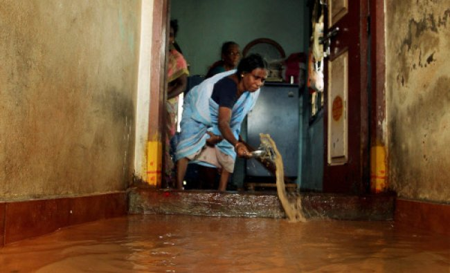 A woman trying to drain the rain water from her house after heavy rains in Chennai on Thursday. PTI