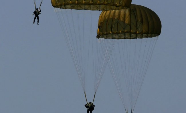 Members of the South Korean Marine Corps parachute from CH-47 helicopter during a ceremony to...