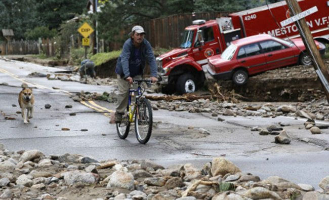 A resident rides down Main Street with his dog in Jamestown, Colorado, after a flash flood...