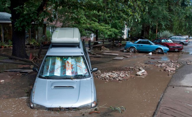 This photo taken on Friday, Sept. 13, 2013, shows vehicles damages by flood waters on a street in...